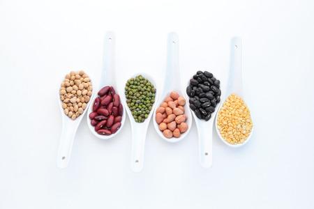 leguminosas: Conjunto de la colección de los granos, las legumbres, los guisantes, las lentejas en cucharas de cerámica aislados sobre fondo blanco.