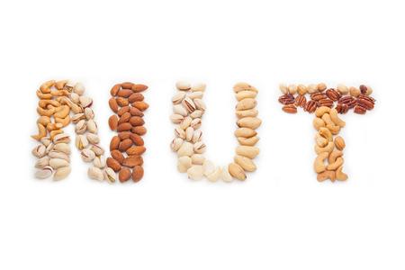 Noten woord van gemengde noten op een witte achtergrond. Stockfoto