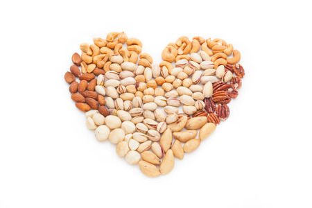 Heart shape made of mixed nuts isolated on white background.