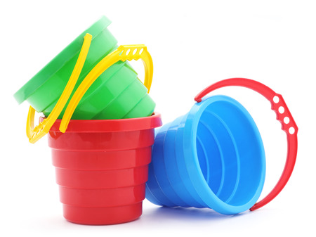 playthings: Childrens plastic buckets  on a white background.
