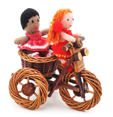 rag wheel: Knitted woolen dolls on toy bike on a white background.