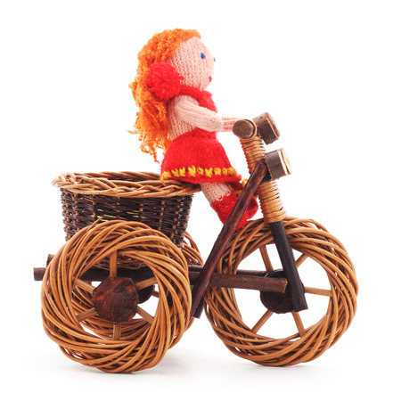 rag wheel: Knitted woolen doll on toy bike on a white background.