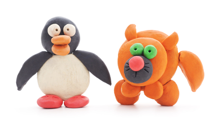 Plasticine cat and penguin on a white background.