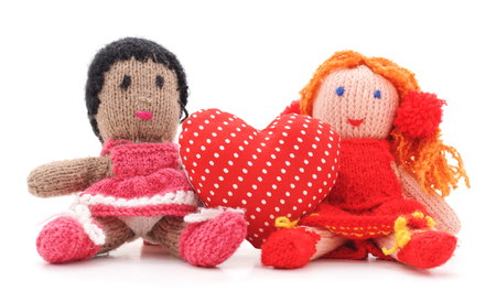 Knitted dolls and toy heart on a white background.