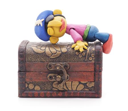 Plasticine pirate on treasure chest on a white background.