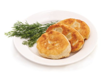 Fried pies with dill on a white plate isolated. Standard-Bild - 115309159