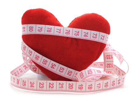Heart and centimeter tape isolated on a white background. Standard-Bild - 116057383