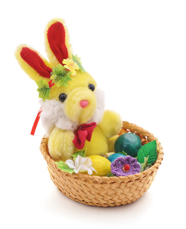 Toy rabbit in Easter basket on a white background.