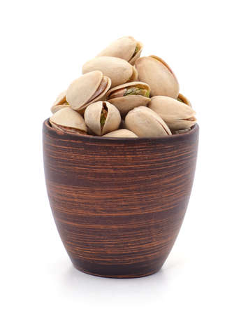 Bunch of pistachios in shell and cup isolated on a white background.