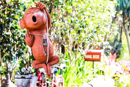 The clay statue is a monkey hanging rope to decorate the garden or restaurant is very popular. Stock Photo