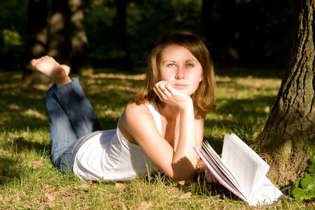 The young girl lies on a grass and reads the book Stock Photo - 5827232