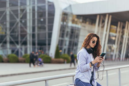 Young beautiful teen woman waiting for a taxi at the airport enjoys the phone with suitcases Reklamní fotografie