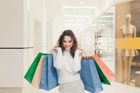 Beautiful brunette girl, with curly hair, chooses clothes in a boutique. In a modern clothing store, for a period of discounts, walks around the supermarket, and holds in his hands colored gift bags