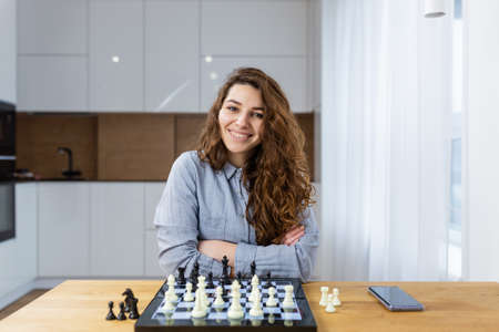 Beautiful girl sitting at home and playing chess online with a laptop