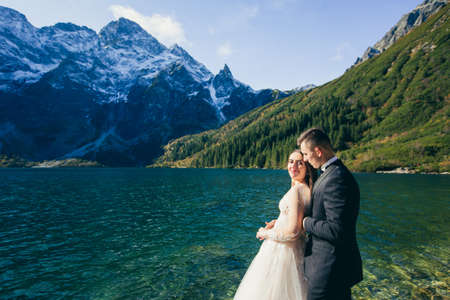 Wedding photo shoot, a young couple in love in the mountains near a large beautiful lake