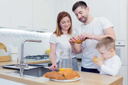 Young happy family with two young sons preparing breakfast together in their kitchen