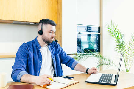 The man uses a headset with a microphone, makes an online video call, for consultations, with the help of a laptop, works at home Archivio Fotografico