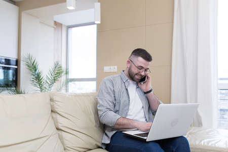 respectable handsome man working from home office, sitting on sofa with laptop, and solving business case