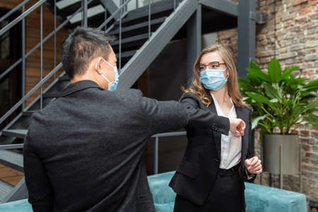 Male and female businesspeople concluding a business meeting are greeted by touching their elbows to each other, wearing protective medical masks