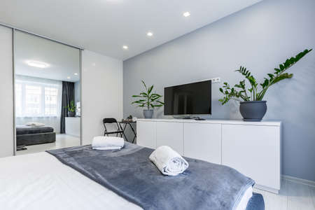 Interior photography, bedroom, in a small studio apartment, with a large bed and white walls