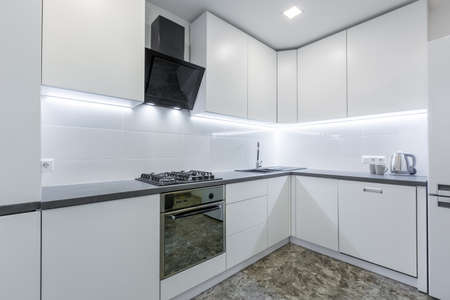 Interior photo, modern kitchen, in light white tones, with black marble tiles on the floor, placed in a small apartment