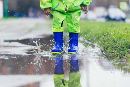 Close-up photo of a little girl jumping in boots on puddles, blue boots