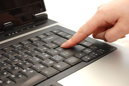 finger typing on a laptop - press enter  photo