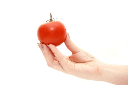 ailment: The female hand holds a tomato on a white background