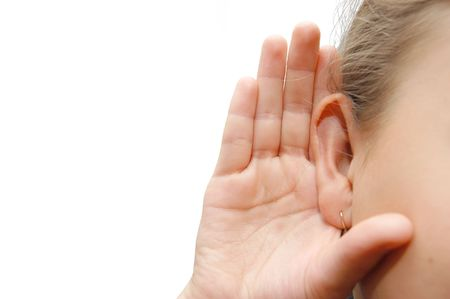 listening ear: Girl listening with her hand on an ear Stock Photo