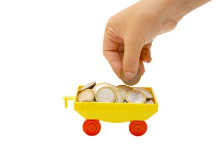 Toy train carrying coins on a white background photo