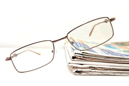 evening newspaper: a few fresh newspaper with the pair of glasses on the table     Stock Photo