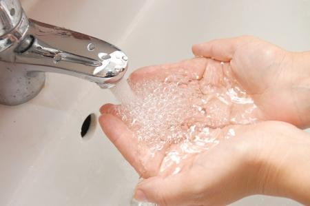 to soak: woman washing hand under running