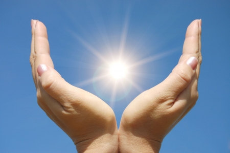 open arms: Female hands touching the Sun     Stock Photo