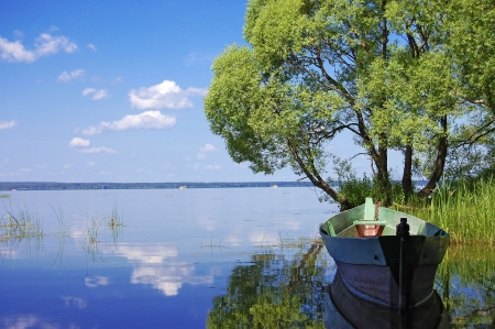 Wooden boat on the bank of lake photo