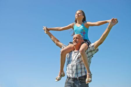 grand parents: grandfather with the grand daughter against the dark blue sky Stock Photo