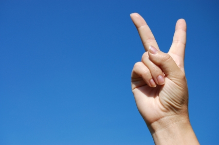 Victory sign against blue sky photo