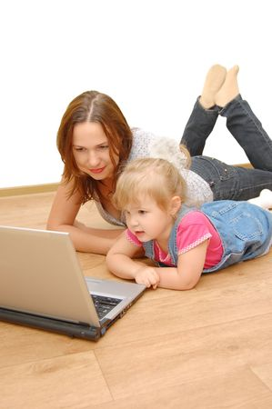 Mother and daughter with laptop on wooden  floor photo