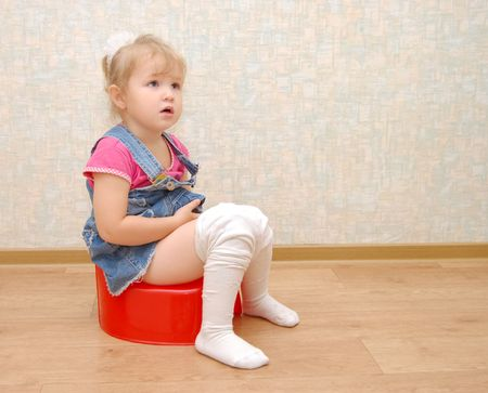 potty: Pretty girl and red potty on wooden  floor