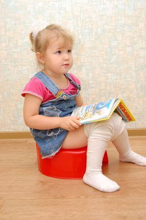 vasino: Bambina seduta sul vasino rosso con libro aperto