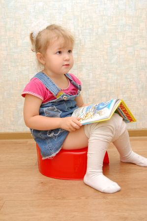 urinating: Little girl sitting on red potty with open book