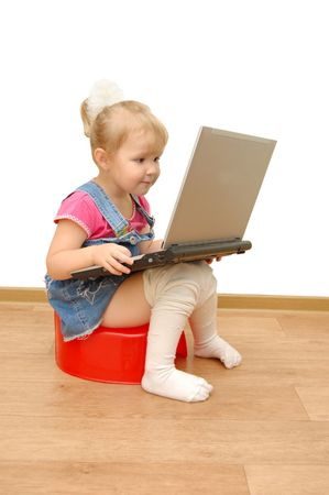 Little girl sitting on red potty with computer photo