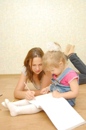 young mother with her daughter lying on the floor and drawing     photo