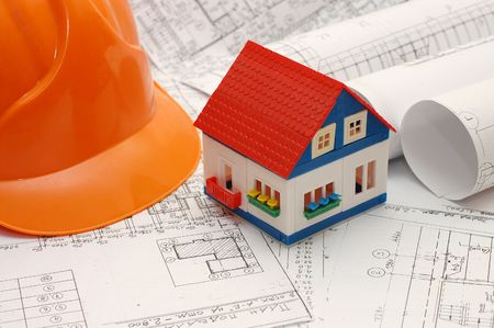 Close-up of toy house model on blueprints with helmet near by Stock Photo - 5521267