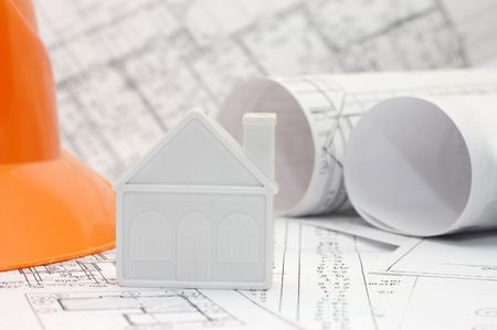 Close-up of toy house model on blueprints with helmet near by Stock Photo - 5521440