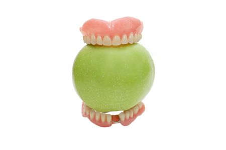 surrogate: Dentures with green apple, isolated on a white background