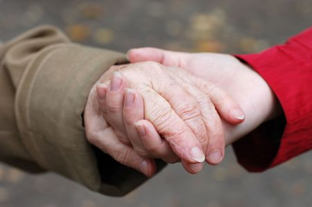 senescence: closeup of a grandfather holding his grand daughter hand