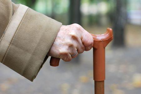 Vieja mano se apoya en un bastón Foto de archivo