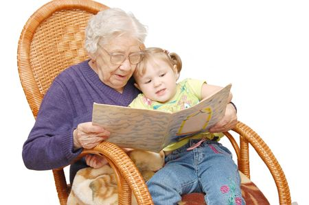 granddaughters: Grandmother reads to the granddaughter in an armchair Stock Photo