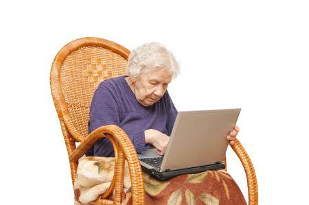 abuela: La abuela con la computadora port�til en un sill�n Foto de archivo