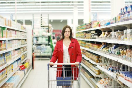 Beautiful young woman standing with a trolley at a supermarket   photo